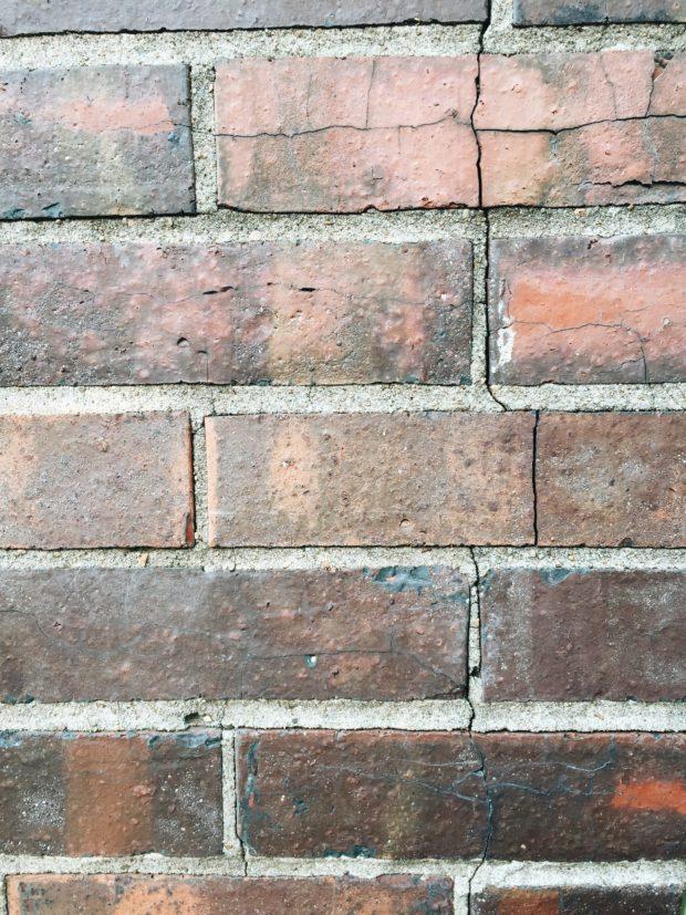A cracked, brick fireplace.