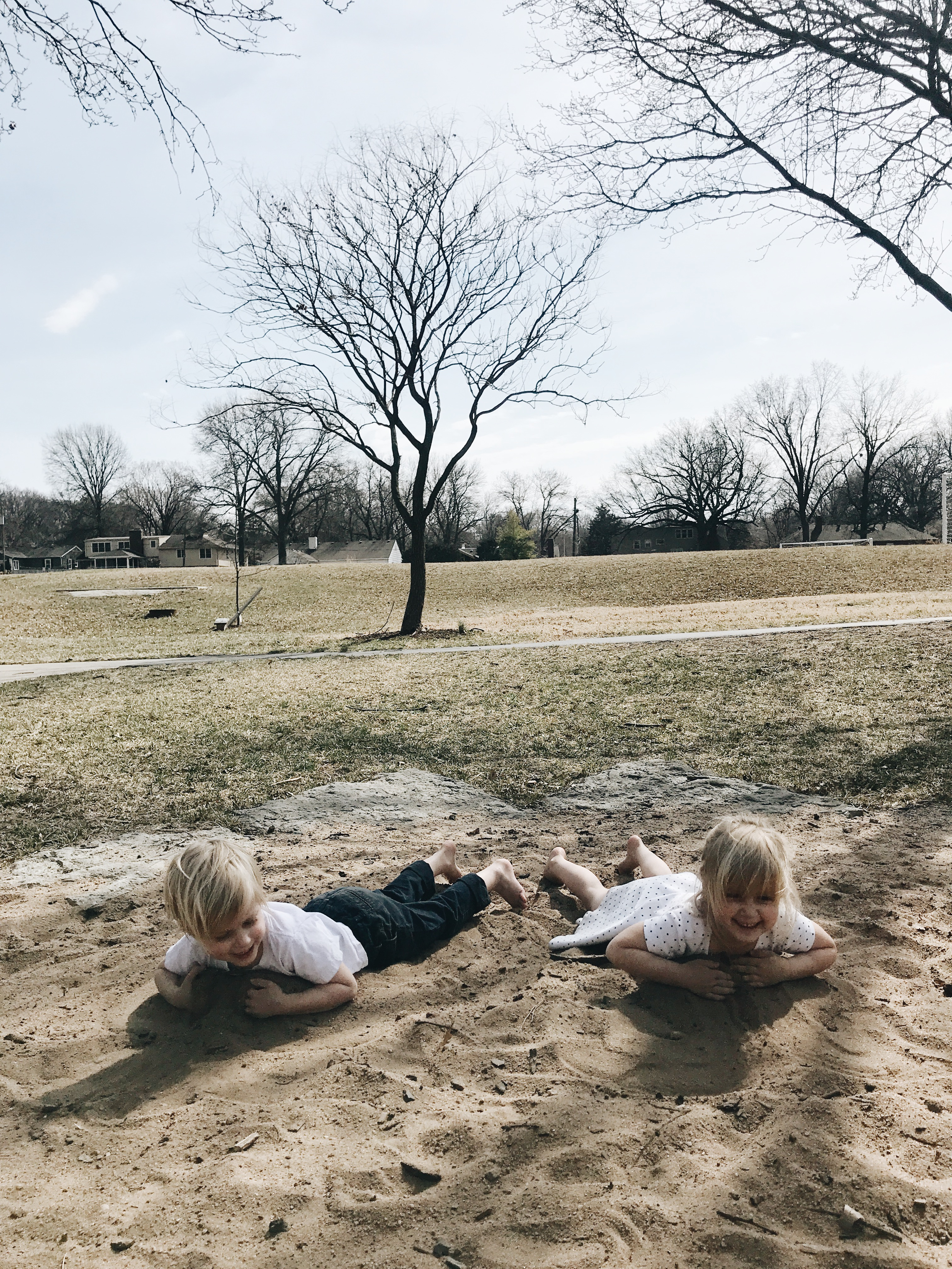 kids in white clothing in sand pit